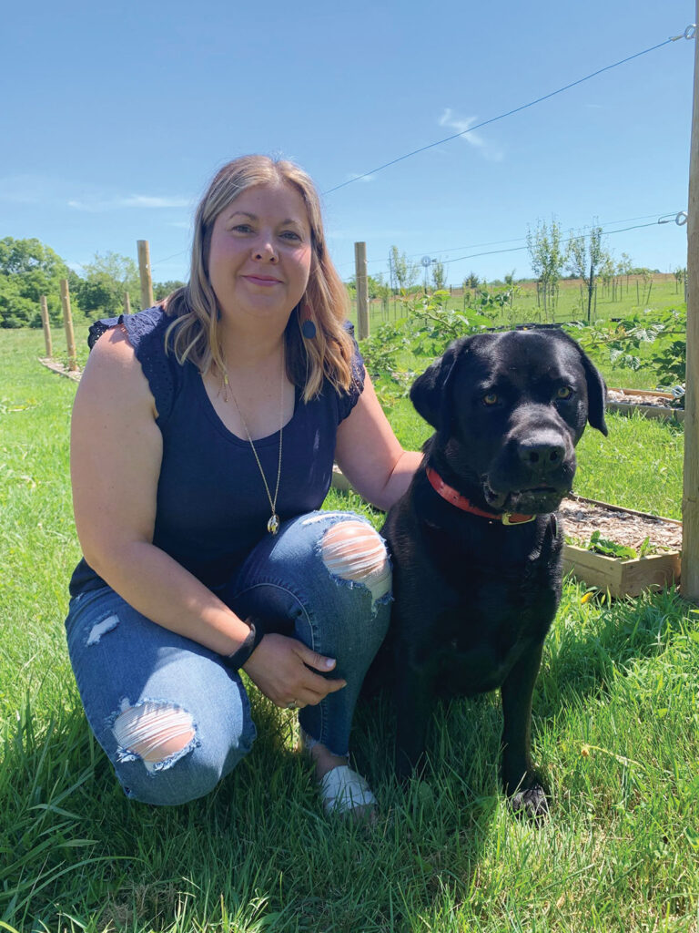 Crystal Dugas with her dog at Black Dog Farm in Marshfield, Missouri. She grows a variety of fruits and vegetables that are sold at local retailers like Mama Jeans Natural Market in Springfield. Photo by Amanda Bradley.