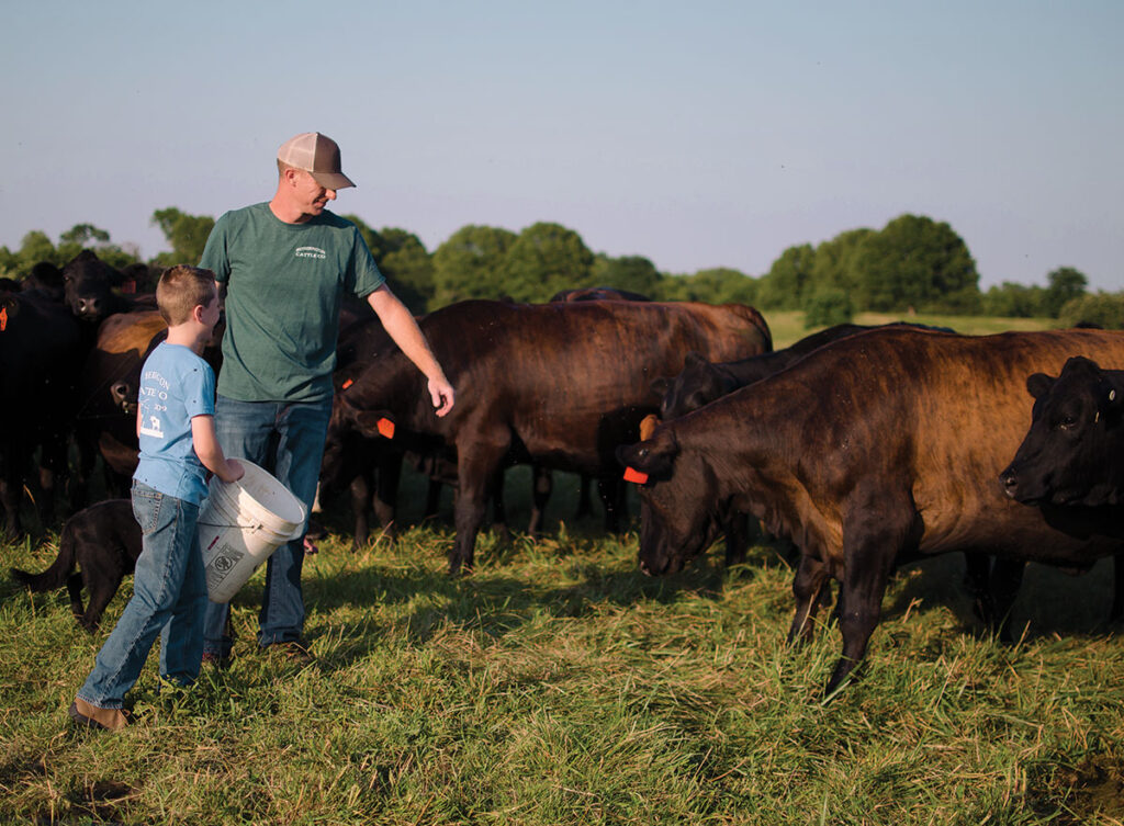 Clint Hetherington and his son Cole feeding cattle. Photo by Ashley Wilson.