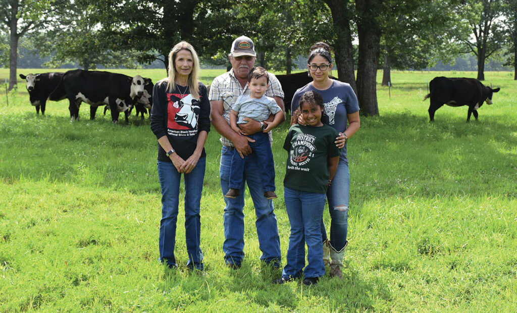 Three generations of the Studdard family work to raise high-quality Black Herefords. Pictured, from left, are Barb Studdard, John Studdard (holding grandson Michael), and Barb and John's daughter Maria and granddaughter Shandon. Photo by Jessica Wilson.